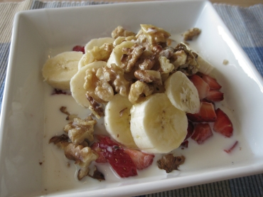 Walnuts, bananas, strawberries, and milk cover the bowl of oatmeal.