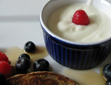 A small bowl of yogurt with multigrain pancakes and berries.
